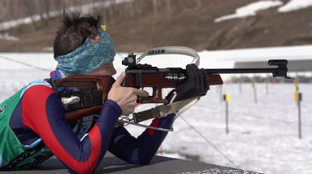 prone position : Biathlete aiming, rifle shooting, reloading rifle in prone position. Junior biathlon competitions East of Cup. Sportsman biathlete Ivan Solodikov in shooting range. Kamchatka, Russia - April 14, 2019. Stock Footage