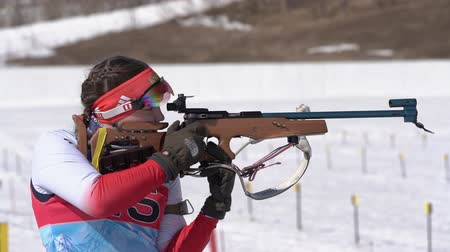 gunshot : Sportswoman biathlete aiming, rifle shooting standing position. Biathlete Babkina Maria in shooting range. Junior biathlon competitions East Cup. Kamchatka Peninsula, Russian Far East - April 14, 2019