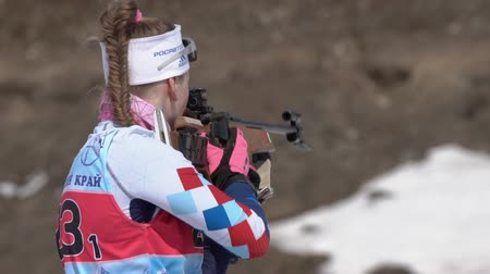 biathlete : Biathlete Shishkina Vlada Saint Petersburg in shooting range. Sportswoman biathlete aiming, rifle shooting standing position. Junior biathlon competitions East Cup. Kamchatka, Russia - April 14, 2019.