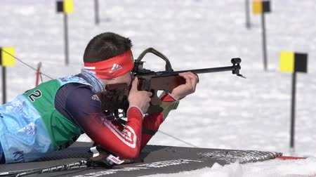 prone position : Biathlete aiming, rifle shooting, reloading rifle prone position. Sportsman biathlete Kapustin Aleksandr in shooting range. Junior biathlon competitions East of Cup. Kamchatka, Russia - April 14, 2019