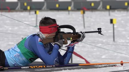 gunshot : Junior biathlon competitions East of Cup. Sportsman biathlete Sporshev Nikita in shooting range. Biathlete aiming, rifle shooting, reloading rifle in prone position. Kamchatka, Russia - April 14, 2019 Stock Footage