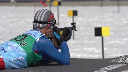 gunshot : Sportsman biathlete aiming, rifle shooting, reloading rifle in prone position. Cheon Yunpil South Korea in shooting range. Junior biathlon competitions East of Cup. Kamchatka, Russia - April 14, 2019.