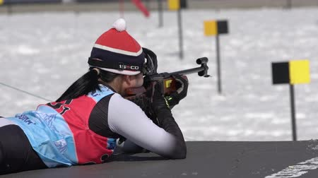 biathlete : Sportswoman biathlete aiming, rifle shooting, reloading in prone position. Biathlete Choi Yoonah South Korea in shooting range. Junior biathlon competitions East Cup. Kamchatka, Russia - Apr 14, 2019.