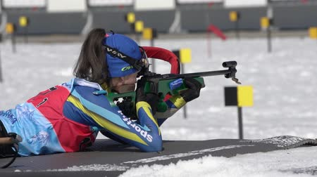 golyó : Sportswoman biathlete aiming, rifle shooting, reloading prone position. Junior biathlon competitions East Cup. Biathlete Arina Kryukova Kazakhstan in shooting range. Kamchatka, Russia - April 14, 2019