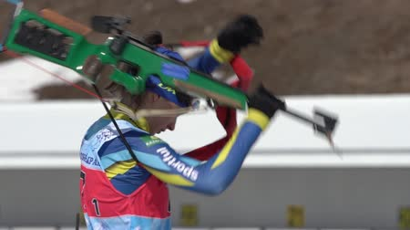 gunshot : Kazakhstan biathlete Kryukova Arina in shooting range. Sportswoman biathlete aiming, rifle shooting, reloading prone position. Junior biathlon competitions East Cup. Kamchatka, Russia - April 14, 2019