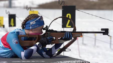 gunshot : Sportswoman biathlete aiming, rifle shooting prone position. Biathlete Galitsyna Ekaterina Saint Petersburg in shooting range. Junior biathlon competitions East Cup. Kamchatka, Russia - Apr 14, 2019