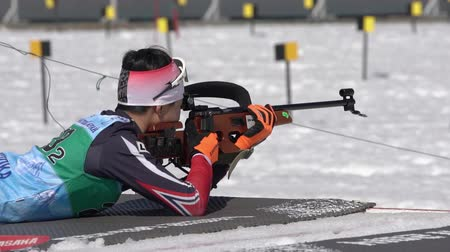 prone position : Sportsman biathlete aiming, rifle shooting, reloading rifle in prone position. Kim Minsu South Korea in shooting range. Junior biathlon competitions East of Cup. Kamchatka, Russia - April 14, 2019.
