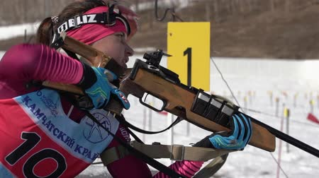 golyó : Sportswoman biathlete aiming, rifle shooting in prone position. Biathlete Ivchenko Anastasia in shooting range. Junior biathlon competitions East of Cup. Kamchatka, Russian Far East - April 14, 2019