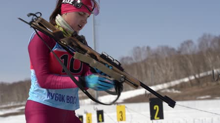 reloading : Junior biathlon competitions East of Cup. Biathlete aiming, rifle shooting in prone position. Sportswoman biathlete Ivchenko Anastasia in shooting range. Kamchatka, Russian Far East - April 14, 2019