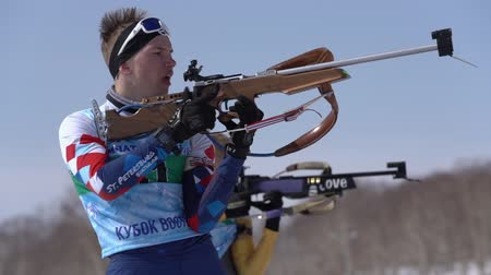 gunshot : Sportsman biathlete aiming, rifle shooting and reloading in standing position. Biathlete Yaroslav Khmara in shooting range. Junior biathlon competitions East of Cup. Kamchatka, Russia - April 14, 2019