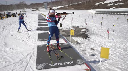 biathlon : Sportswoman biathlete aiming, rifle shooting in standing position on shooting range stadium. Biathlete Shishkina Vlada. Junior biathlon competitions East of Cup. Kamchatka, Russia - April 14, 2019.