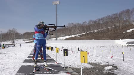 golyó : Sportswoman biathlete Vlada Shishkina aiming, rifle shooting in standing position on shooting range arena. Junior biathlon competitions East Cup. Kamchatka Peninsula, Russian Far East - Apr 14, 2019. Stock mozgókép
