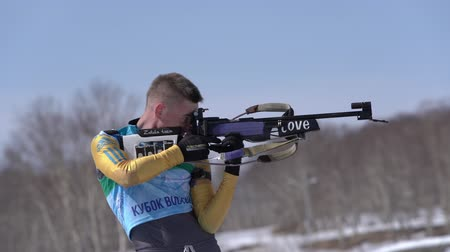 gunshot : Biathlete aiming, rifle shooting, reloading standing position. Sportsman biathlete Vadim Kurales Kazakhstan in shooting range. Junior biathlon competitions East Cup. Kamchatka, Russia - April 14, 2019 Stock Footage