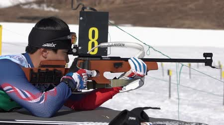 posição : Korean sportsman biathlete aiming, rifle shooting, reloading rifle in prone position. Yang Seon Jik in shooting range. Junior biathlon competitions East Cup. Kamchatka Peninsula, Russia - Apr 14, 2019