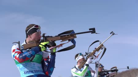 biathlete : Sportsman biathlete aiming, rifle shooting and reloading in standing position. Biathlete Dionis Roduner in shooting range. Junior biathlon competitions East of Cup. Kamchatka, Russia - April 14, 2019.
