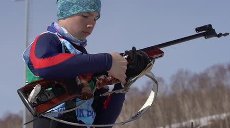 biathlon : Sportsman biathlete reloading rifle in shooting range. Biathlete Solodikov Ivan during Junior biathlon competitions East Cup. Petropavlovsk City, Kamchatka Peninsula, Russian Far East - April 14, 2019