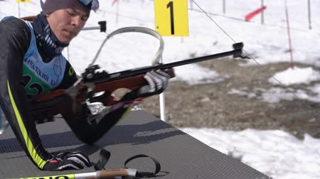 gunshot : Junior biathlon competitions East Cup. Sportsman biathlete Vyacheslav Konovalov in shooting range. Biathlete aiming, rifle shooting, reloading rifle in prone position. Kamchatka, Russia - Apr 14, 2019