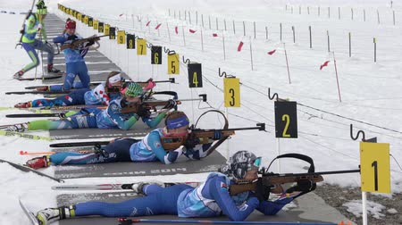 posição : Group sportswoman biathlete aiming, rifle shooting and reloading rifle in prone position. Biathletes shooting range during Junior biathlon competitions East of Cup. Kamchatka, Russia - April 13, 2019.