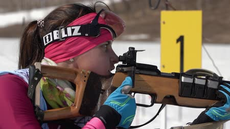 biathlete : Biathlete aiming, rifle shooting in prone position. Sportswoman biathlete Ivchenko Anastasia in shooting range. Junior biathlon competitions East of Cup. Kamchatka, Russian Far East - April 14, 2019