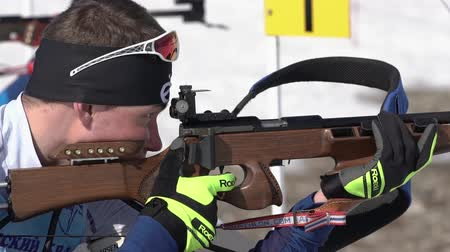biathlete : Sportsman biathlete aiming, rifle shooting, reloading rifle in prone position. Biathlete Dionis Roduner in shooting range. Junior biathlon competitions East of Cup. Kamchatka, Russia - April 14, 2019