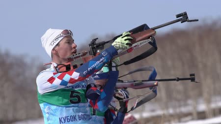 gunshot : Junior biathlon competitions East Cup. Sportsman biathlete aiming, rifle shooting, reloading standing position. Biathlete Akhtyamov Ilmir in shooting range. Kamchatka Peninsula, Russia - Apr 14, 2019