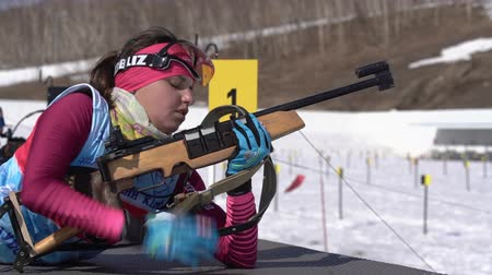 prone position : Junior biathlon competitions East Cup. Sportswoman biathlete aiming, rifle shooting in prone position. Biathlete Anastasia Ivchenko in shooting range. Kamchatka Peninsula, Russia - April 14, 2019