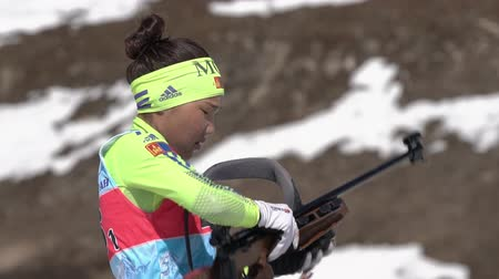 moğolistan : Mongolian sportswoman biathlete reloading rifle before shooting. Biathlete Doljinsuren Munkhbat in shooting range. Junior biathlon competitions East Cup. Kamchatka Peninsula, Russia - April 14, 2019 Stok Video