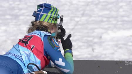 biathlete : Sportswoman biathlete aiming, rifle shooting standing position. Biathlete Legostaeva Anastasia in shooting range. Junior biathlon competitions East of Cup. Kamchatka Peninsula, Russia - April 14, 2019