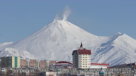 fumarole : Winter city scape of Petropavlovsk-Kamchatsky City and fumaroles activity of active Avacha Volcano in sunny weather with clear sky. Petropavlovsk City, Kamchatka Peninsula, Russia - January 23, 2020