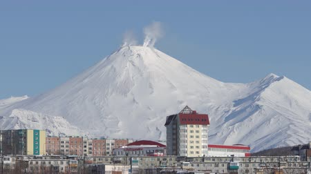 petropavlovsk : Winter cityscape of Petropavlovsk-Kamchatsky City and activity of active Avachinsky Volcano in sunny day, clear blue sky. Time-lapse. Petropavlovsk City, Kamchatka Peninsula, Russia - January 23, 2020 Stock Footage