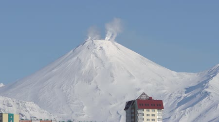russian far east : Winter townscape of Petropavlovsk-Kamchatsky City and active Avachinsky Volcano in sunny day with clear blue sky. Zoom in time-lapse. Petropavlovsk City, Kamchatka Peninsula, Russia - January 23, 2020