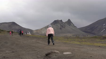 uzak : Woman hiker walking on country road in mountains for traveling, vacation, observing wildlife in popular travel destinations. Avacha Volcano, Kamchatka Peninsula, Russian Far East - August 30, 2019.