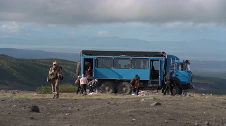 wspinaczka : Group of travelers unloads off-road extreme expedition truck in mountains for vacation and camping in popular travel destinations. Avacha Volcano, Kamchatka Peninsula, Russian Far East - Aug 30, 2019.