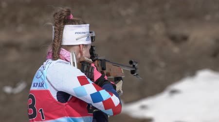 ジュニア : Sportswoman biathlete aiming, rifle shooting, reloading in standing position. Biathlete Shishkina Vlada in shooting range. Junior biathlon competitions East of Cup. Kamchatka, Russia - April 14, 2019. 動画素材