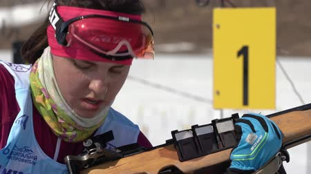 biathlete : Sportswoman biathlete aiming, rifle shooting in prone position. Biathlete Anastasia Ivchenko in shooting range. Junior biathlon competitions East of Cup. Kamchatka Peninsula, Russia - April 14, 2019 Stock Footage