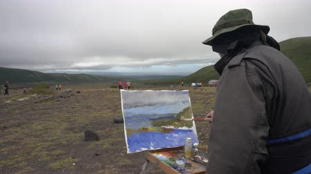 toendra : Creative painter draws brush oil paints on canvas autumn mountains landscape, standing in open air in tundra during gloomy cloudy weather. Avacha Volcano, Kamchatka Peninsula, Russia - August 30, 2019 Stockvideo