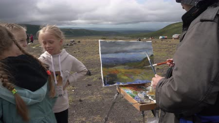 handheld shot : Group of children - boys and girls are watching professional creative artist paints on canvas autumn mountain landscape. Avacha Volcano, Kamchatka Peninsula, Russian Far East - August 30, 2019. Stock Footage