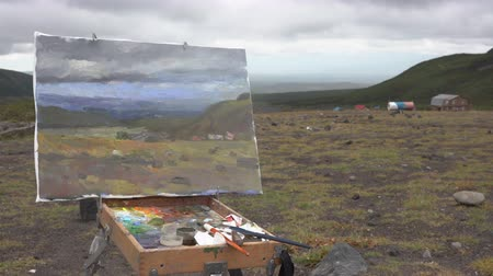 toendra : Oil painting with autumn mountain landscape painted on cloudy day, gloomy weather. Canvas stands on an easel in open air in tundra. Avacha Volcano, Kamchatka Peninsula, Russia - August 30, 2019.