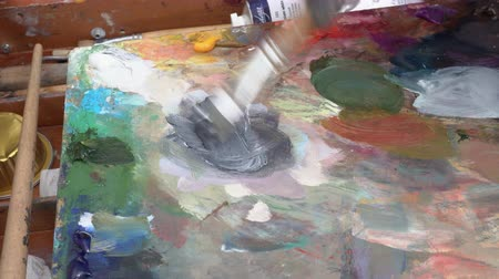 daleko : Creative painter mixing palette of oil paints in palette on easel. Close-up view. Avacha Volcano, Kamchatka Peninsula, Russian Far East - August 30, 2019.