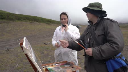 handheld shot : Artist master teaching student girl to paint mountain landscape in autumn cloudy weather outdoors in mountainous area. Avacha Volcano, Kamchatka Peninsula, Russia - August 30, 2019.
