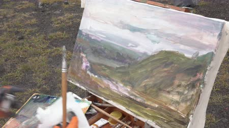 handheld shot : Artist draws brush oil painting on canvas autumn mountains landscape during beautiful gloomy cloudy weather. Avacha Volcano, Kamchatka Peninsula, Russian Far East - August 30, 2019.