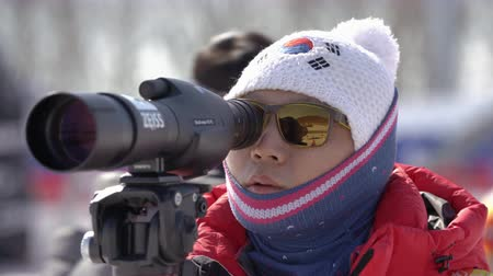 biathlon : Junior biathlon competitions East of Cup. Instructor of South Korea biathlon team watches biathletes in monocle at shooting range biathlon arena. Kamchatka Peninsula, Russian Far East - April 14, 2019