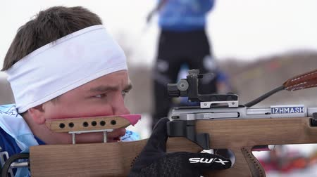 reloading : Sportsman biathlete rifle shooting, aiming and reloading rifle in prone position. Biathlete Krutov Andrey in shooting range. Youth biathlon competitions East Cup. Kamchatka, Russia - April 12, 2019.