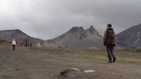 패스 : Male photographer with backpack hiking on country road in mountains for vacation, observing wildlife in popular travel destinations. Avacha Volcano, Kamchatka Peninsula, Russia - August 30, 2019. 무비클립