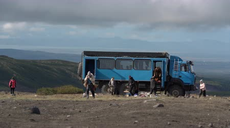 bergbeklimmer : Group tourists unloads off-road extreme expedition truck in mountains for vacation in popular travel destinations. Time lapse. Avacha Volcano, Kamchatka Peninsula, Russian Far East - August 30, 2019.