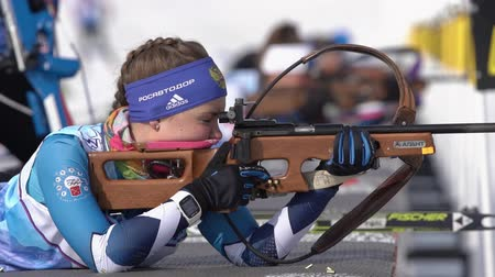 Sportswoman biathlete aiming rifle shooting in prone position. Biathlete Galitsyna Ekaterina Saint Petersburg in shooting range. Junior biathlon competitions East Cup. Kamchatka, Russia - Apr 13, 2019