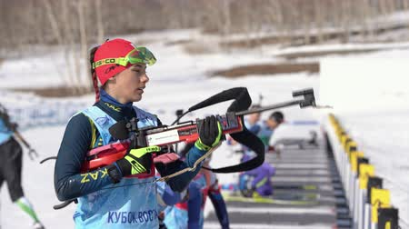 Sportswoman biathlete aiming, rifle shooting in standing position. Biathlete Polina Yegorova Kazakhstan in shooting range. Junior biathlon competitions East Cup. Kamchatka, Russia - Apr 14, 2019.