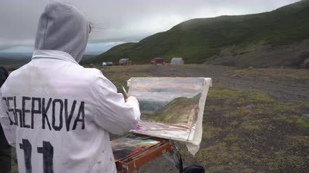 Young creative artist enthusiastically draws brush oil paints on canvas autumn mountains landscape, standing in open air. Avacha Volcano, Kamchatka Peninsula, Russia - August 30, 2019. Стоковые видеозаписи