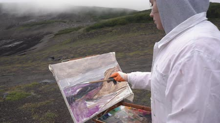 Young woman creative painter draws brush oil paints on canvas autumn mountains landscape, standing in open air in tundra. Avacha Volcano, Kamchatka Peninsula, Russian Far East - August 30, 2019.