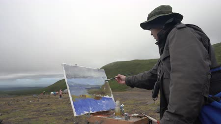 Creative painter draws brush oil paints on canvas mountains landscape, standing in open air in tundra during autumn gloomy cloudy weather. Avacha Volcano, Kamchatka Peninsula, Russia - August 30, 2019